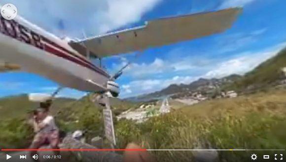【危機一髪動画】低空飛行の飛行機に頭をフッ飛ばされそうになった旅行者が激写される